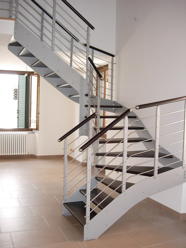 Metal British: double lateral structure in painted steel, wood treads, one-side railing formed from plates in painted steel and horizontal stainless steel wires, handrail in stainless steel or wood.